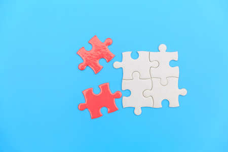 jigsaw puzzle on a blue background. Completing final task, missing jigsaw puzzle pieces and business concept with a puzzle piece missing.