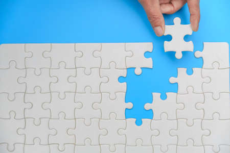 Closeup hand of woman connecting jigsaw puzzle, Business solutions, success and strategy concept Фото со стока