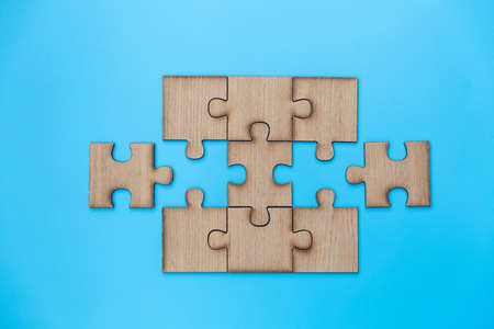 Unfinished jigsaw puzzle pieces on blue background,  Copy space. Фото со стока