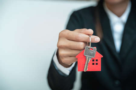 House key in hand, Female hand holding house key, real estate agent.