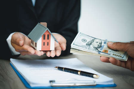 Hands giving house model to other hands with money. Concept of real estate.
