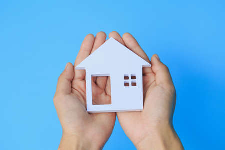 Hands holding house on a blue background, family home and protecting insurance concept