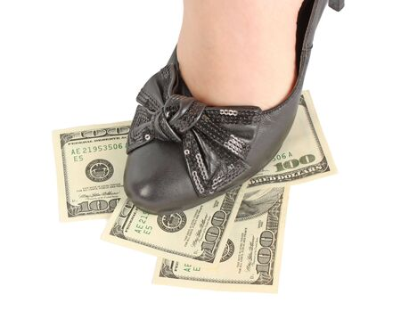 Female leg in black shoes on dollar banknotes, business concept photo