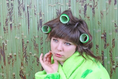 dressing gown: beautiful girl in green dressing gown with rollers hair Stock Photo