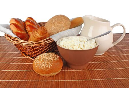 Fresh breads and milk in jug and glass, cottage cheese in bowl, food photo photo