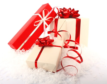heap snow: Christmas gift boxes with ribbon and bow on snow, Christmas decorations