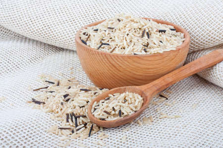Raw wild rice in wooden bowl and spoon on burlap, food ingredient photo Stock Photo