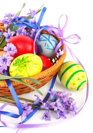 Colorful painted Easter eggs with violet flowers and ribbons in wooden basket