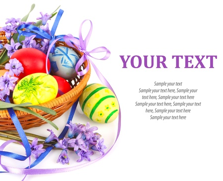 Colorful painted Easter eggs with violet flowers and ribbons in wooden basket photo