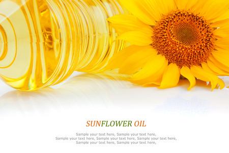 Zonnebloemolie in plastic flessen en gele bloem op wit, voedselingrediënt Stockfoto