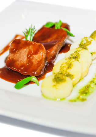 ingestion: Meat with potatoes in red sauce on plate restaurant menu