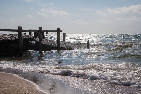 SEA  LANDSCAPE: Old wooden pier sea landscape with sky and sand