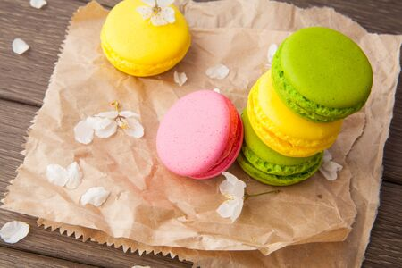 refined: Macaroon, refined tasty dessert and flowers on wooden, food photo