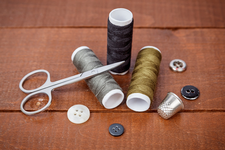 kit de costura: Scissors and thread coils on wooden, sewing tools and sewing kit photo Foto de archivo
