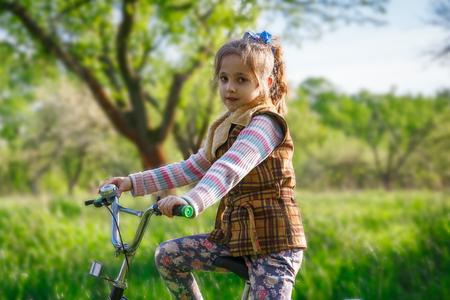 Little girl on bike on the grass near spring garden, lifestyle photo Stock Photo