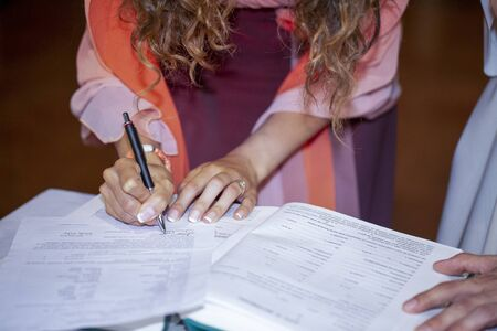 female witness signing marriage certificate in Christian marriage Foto de archivo