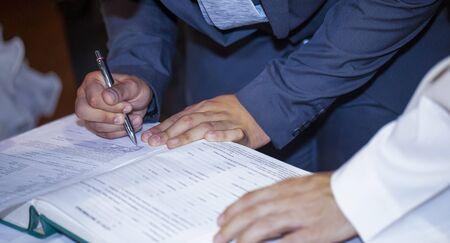 groom signs wedding deed in marriage hands