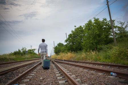man with suitcase along train tracks failing job loss