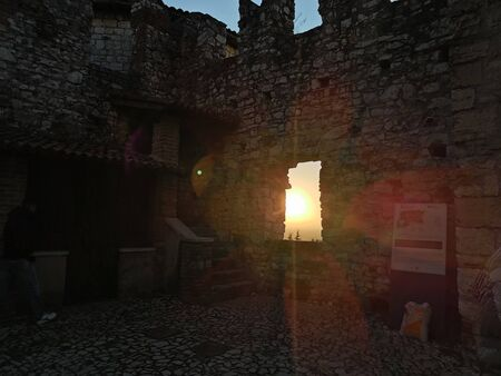 beautiful setting sun in ancient medieval window with yellow light