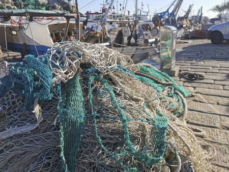 fishing net rolled up in a basket on the harbor quay