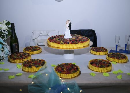 beautiful fruit wedding cake with statue of the bride and groom