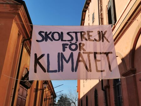 sign between buildings against climate change