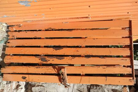 old orange wooden bench with peeling paint