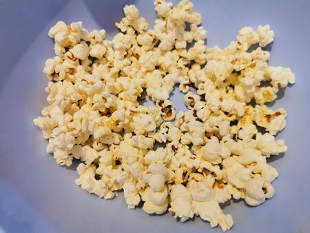freshly made popcorn in bowl taken by girl hand Foto de archivo