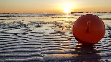 sunrise on the beach of the mediterranean sea in riccione rimini with sun reflected sand and waves orange sea boa