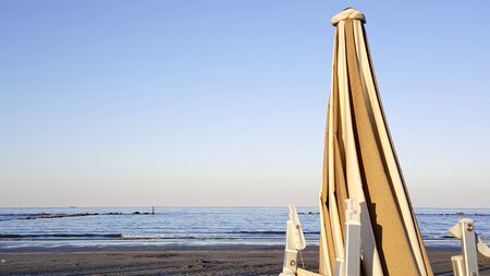 umbrellas and deckchairs closed at dawn on the rimini of rimini with sun rumbrellas and deckchairs closed at dawn on the rimini of rimini with sun reflecting off the wateeflecting off the wate. High quality photo