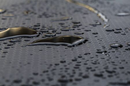 water tears on black drops and water deposit on black rubber surface with sun reflection