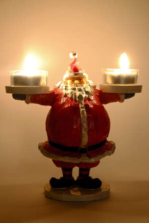 christmas statue of santa claus isolated on white background with candle holder tealights in hands. High quality photo