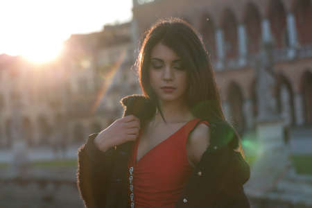 beautiful girl with long mediterranean black hair at sunset in the square of padua. High quality photo