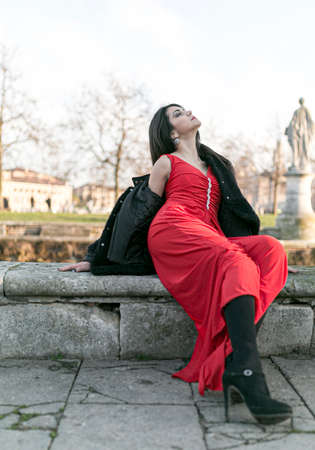 beautiful girl with long black hair at sunset lying in the square in padua. High quality photo Stockfoto