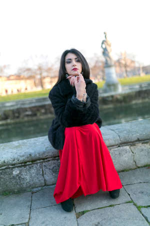 beautiful girl with long black hair at sunset sitting in the square in padua. High quality photo