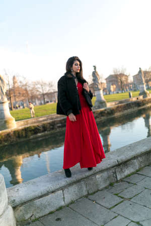 beautiful girl with long black hair standing at the edge of the canal in the square in padua. High quality photo