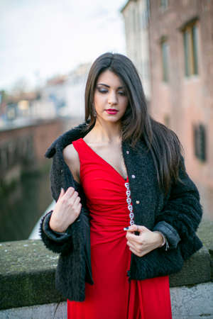 beautiful girl with long black mediterranean hair posing with long red dress. High quality photo