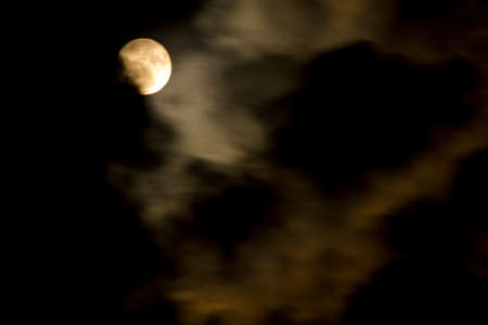 Orange full moon behind clouds on a dark night. High quality photo