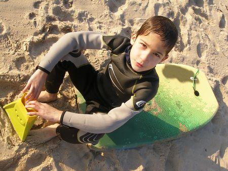 bodyboard: a boy sitting on his bodyboard board