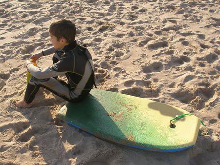 a boy sitting on his bodyboard board Stock Photo - 404207