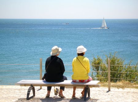 two women sittings watching the sea