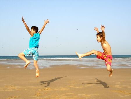Two boys jumping of joy on the beach