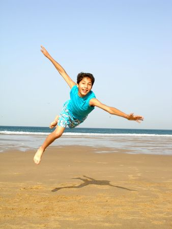 a boy jumping on the beach