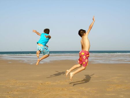 Two boys jumping of joy on the beach Stock Photo - 434854