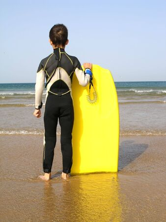 A boy, with its body board, is evaluating the surf Stock Photo - 433859