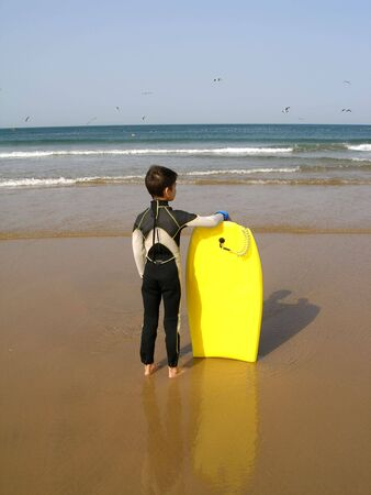 A boy, with its body board, is evaluating the surf
