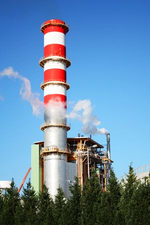 Power plant chimney producing white smoke against a blue sky photo