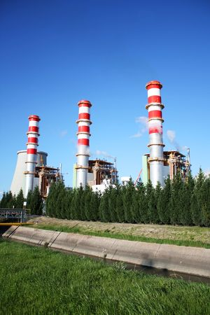 Power plant chimneys producing white smoke against a blue sky