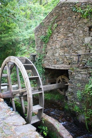 Old watermill with a wooden wheel and stone walls photo