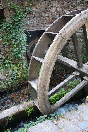 molino de agua: Antiguo molino de agua con una rueda de madera y paredes de piedra